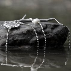 Neckless with hand casted branch, silver inlaid beach stone and a fresh water pearl.