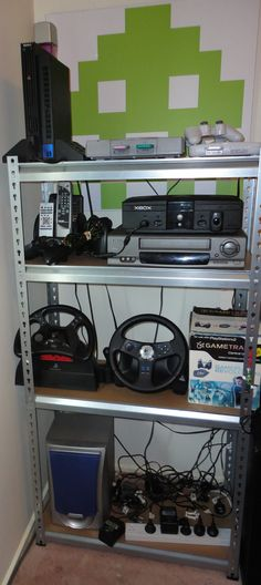 The Sony Playstation shelf, original Xbox, some remote, steering wheels (both are Playstation wheels), a fire hazard of power cables and a custom Space Invader print that has been printed on 20mm foamboard with black edging.