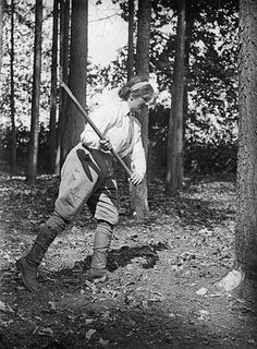 A member of the Women's Forestry Corps, part of the Women's Land Army, begins cutting down a tree during the First Wold War.