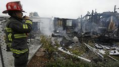 Napa Fire Captain Steve Becker inspects mobile homes which were destroyed Sunday, Aug. 24, 2014, at the Napa Valley Mobile Home Park, in Napa, Calif.