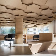 Interior of a Parisian salon in which the ceiling is layered with hexagonal plywood cutouts. Designed by Joshua Florquin to recall a forest canopy. Les Dada East hair salon.