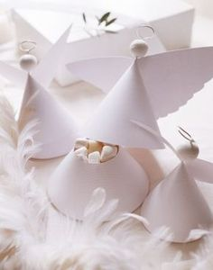 Gift boxes in the shape of little angels made with white paper, wire and iron and party favors.