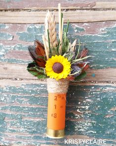 Orange Shot Gun Shell with a Sunflower Boutonniere This listing is for 1 Fancy Boutonniere that features an Sunflower Paper Flower, a cluster of Dried Wheat, Thistle, Dried Grasses and Fancy Feathers for accent. Spun with twine this unique boutonniere is snuggled into a Rustic Orange Shot Gun Shell. Perfect and crafted for a Country Outdoorsy themed Wedding. Give him a Boutonniere that he will LOVE wearing.  The shell itself is a bit rusted to give that rustic country feel.  Measures approx…