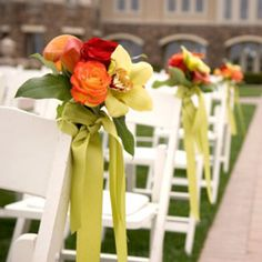 Bouquets of roses and calla lilies with wine ti-leaves looped in place of the leaves and orchids, tied with gold ribbon