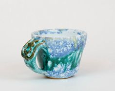 Handmade, hand colored cup with green ornaments, ceramic coffee cup