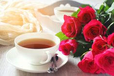 Romantic morning tea  for two - Valentine's Day: Romantic morning Tea Party for two with burning candles and bouquet of red roses. Toned image