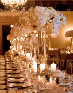 classic and elegant all white wedding decor with beautiful arrangements of flowers + lots of candles