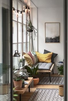 Bench w/ pillows. Strewn lights near window w/ hanging plant. Candles, lanterns, books, painting near bench, small rug, & potted plants