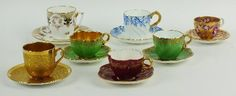 A collection of Coalport cabinet cups and saucers, circa 1891-1919, comprising three miniature quatrefoil examples, two red and one green, green printed mark, 4.5cm high; a plain gilt cup and saucer, pattern 6346/A, 5cm high, a gilt teacup and saucer, printed with red portrait panels and roses and a blue and white example, with gold handle, printed factory marks (14)