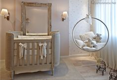 quarto de bebê decorado com balanço de acrílico muito luxuoso, conta com papel de parede delicado e toques de dourado.