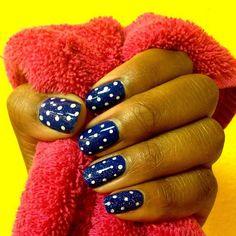 Dark blue nails with white polka dots.