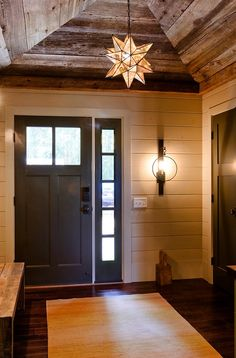 Rustic Foyer with reclaimed barnwood ceiling, shiplap walls, aged iron wall sconce and Moravian Star Pendant light.