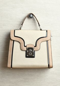 Designed by Melie Bianco, this structured leather bag in beige is accented with black patent trim and silver colored hardware.