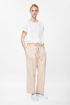 Made from cotton with raw, frayed edges, these trousers are an oversized fit that pull in at the waist with a fabric tie fastening. A loose, straight shape, they have in-seam side pockets and a single welt pocket on the back.