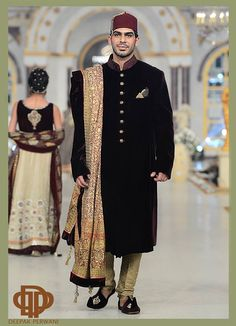A black hand embroidered sherwani with work on the neck with kora, dabka & stones. Paired with a banarsi churidar & a gold screen printed shawl  www.onitaa.co.uk