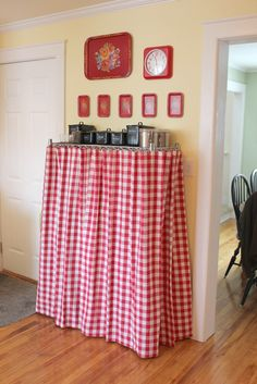 """Wire Shelving Idea:  I love my wire shelving unit for the extra """"pantry"""" storage it provides.  Even with nice storage bins and canisters, it still had a tendency to look cluttered.  These gingham """"curtains"""" are actually 2 hemmed, square tablecloths.  They're hung on IKEA Riktig curtain clips.  (I used a plier to open the clip's attached hook, and to pinch it closed on the top wire).  Now, I don't have to look at my crock-pots, blender etc. :)  #wireshelf #cover #curtain #tablecloth"""