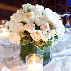 Lush white roses in a leaf-wrapped square vase