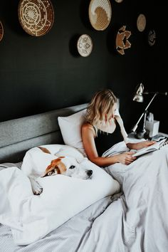 Meg Biram reading in bed with puppy.
