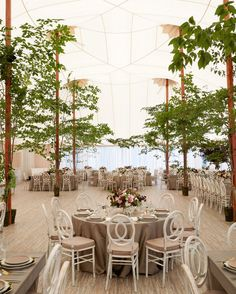With the addition of trees, flooring, and elegant lighting, Easton Events transformed the inside of the reception tent into a sophisticated oasis from the rain.