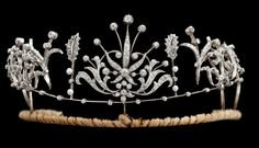 Tiara designed as a series of stylised floral and foliate knifewire sprays, connected by four holly leaf and seed pearl motifs. Associated brooch and earrings similar design, set throughout with old brilliant, single and rose-cut diamonds, mounted in silver and gold. Brooch with partial French maker's mark and French assay marks, tiara detaches to form three brooches, fittings supplied.