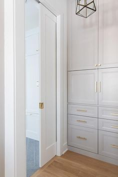 Floor-to-ceiling dove gray laundry room cabinets adorned with brass pulls and knobs are fixed adjacent to a white pocket door opening to a mudroom.