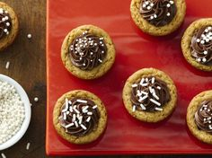 These frosted cookie cups are hiding a delicious secret—chocolate-covered peanut and caramel candy bars are baked into the center of each one!