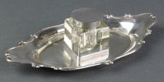 Lot 495, An Edwardian silver quatrefoil ink stand with glass inkwell and silver lid, Chester 1905, est £100-150