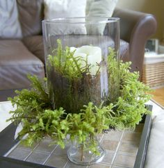mossy candlelit centerpiece made from a vase stacked on top of a cake stand