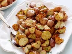 Ina Garten's Garlic-Roasted Potatoes from Food Network's Barefoot Contessa make the perfect classic side dish for any meal.