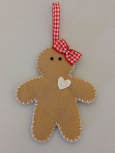 Charming gingerbread girl Christmas decoration handmade in felt with added heart detail, bead eyes and gingham ribbon bow, with matching hanging