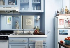 One Kings Lane NYC apartment rental kitchen makeover. light blue kitchen.  Removed doors from cabinets and painted light blue, brass hardware, mirrored backsplash. editor Kerstin Czarra