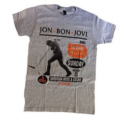 This gray t-shirt announces Jon Bon Jovi Live In Concert at the Hard Rock Hotel & Casino in Las Vegas, NV, 2013. It features a photo of Bon Jovi and the microphone. Material: 90% Ringspun Cotton/10% P