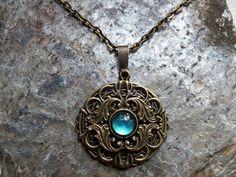 """Der Amulettanhänger der Kette """"Romira"""" ist inspiriert vom Jugendstil und der Ornamentik des Barocks.  Geschmückt wird der Anhänger von zwei verschnörkelten Zierelementen und einem Glascabochon,..."""