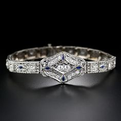 A delightfully distinctive Art Deco bracelet, circa 1930s, glistening with 1.50 carats of Swiss-cut diamonds (old mine single-cut diamonds), accented with royal blue navette shape synthetic sapphires (original to the period). The elaborately ornamented bracelet, crafted in platinum on 14 karat gold, is die-struck and hand finished with delicate decorative open work, milgrained and engraved details. 7 3/8 inches long, 3/4 inch wide.