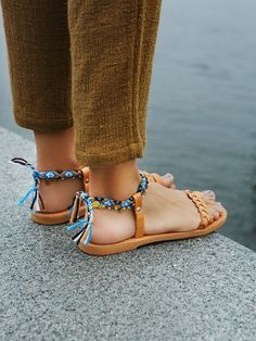 Inspired by the Mediterranean these slip-on leather sandals feature a braided band a toe loop. Fabric woven ankle strap with metal and bead detailing.