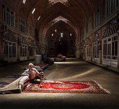 An elderly man sitting on an Iranian hand woven rug in middle of Tabriz Bazaar, IRAN.