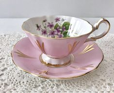Vintage china tea cup and saucer, made by Queen Anne China in England. An avon shaped cup in white and pink with gold details and purple violets on the inside of the cup. It is in good condition, no chips, cracks or crazing. Please Note: The items I sell are not new, they are