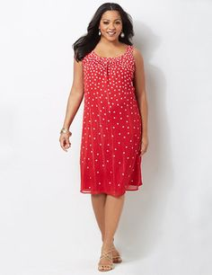 Feminine dress boasts a beautiful polka dot print that playfully scatters at the hem. Metallic yarn cascades down the fabric for added shine. Complete with a banded scoop neckline with falling gathers underneath for a lovely finish. Fully lined. Catherines plus size dresses are expertly designed to flatter your figure. catherines.com