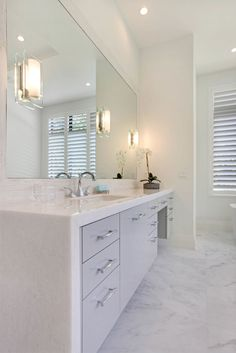 "Master Bath Design by Interior Elementz. Bathroom features include a floating vanity with high gloss white lacquer finish and 2"" mitered edge Calcutta marble waterfall countertop, full height mirror with custom Calcutta marble pencil mosaic frame, a 6' freestanding tub with floor mounted chrome tub filler, and finished off with a frameless glass enclosure shower and infinity drain. Visit our website for complete details!"