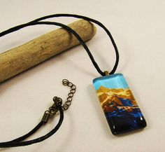 The image inside features Mt. Shuksan during alpine glow. It was from my own personal collection of photographs I took while on a trip to Washington. The backside of the glass tile pendant features a glaze covering with an antique bronze alloy bail attached. On the ends of the black cord is a lobster clasp and an extender.   This glass tile measures 2.4cmx4.8cm (1x1.8) and has a waxed black cord attached that measures 24 (60cm).  These pendants are not waterproof but water resistant.  If any…