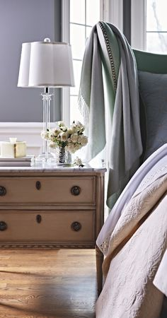 A nonchalant beauty, the Etienne Bedside Chest was inspired by a French antique, with honed Carrera marble top, French blue finish and white edging.  | Frontgate Interiors