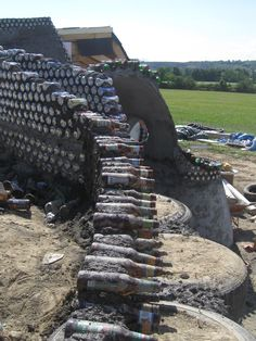 The step by step building of an eco house made with bottles, soda cans, old tires and cement. Earthship Biotecture, Earthship Home, Earthship Design, Bottle House, Bottle Wall, Glass Bottle, Cob Building, Building A House, Green Building
