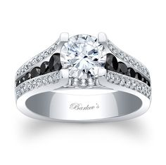 This sophisticated, vintage, white gold, three row black and white diamond engagement ring sports a round prong set diamond center. The shank features three rows, the center row is channel set with black diamonds with flanking rows of pave set round diamonds. A milgrain finish adds the final touch of elegance to this classic ring.<br />  <br />  Also available in rose, yellow gold, 18k and Platinum.