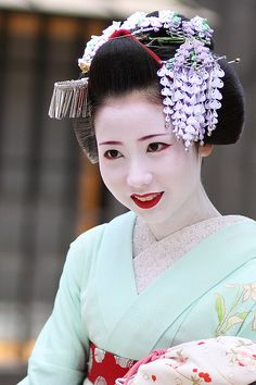 Kyoto, Japan. The colourful flower hairpins that decorate the hair of maiko (apprentice geisha) are known as hana kanzashi. These flower ornaments change monthly to express the season. Mamehana wears a kanzashi of wisteria flowers for May.
