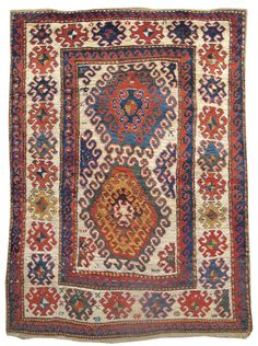 """Kazak, 19th C (4th Q),  Caucasus - A popular aspect of successful Bordjalou Kazaks is their ability to blur the distinction between positive & negative space. This piece draws two colorful medallions, composed of layers of colorful latch-hook ornament. Here the ivory ground itself becomes a large figure eight-shaped tendril. This aesthetic is mirrored in the main border, where negative space in ivory forms half-ornaments of the same type rendered in red, green, blue, & gold. W :4' 10"""" x L…"""