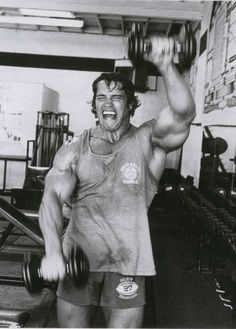 ILYKS.COM - Arnold Schwarzenegger lifting dumbbells straight up in front of him giving it a lot of effort to workout his frontal shoulders like no other bodybuilder F