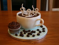 An early mothers day gift for my mum (its mothers day in the UK on April 3rd and I am away!). She loves coffee and chocolate cake. Its a chocolate cake, carved into a cup, filled with chocolate ganache and covered in fondant. Gumpaste 'steam' and cup handle. Fondant 'coffee beans' and a cupcake piped with ganache
