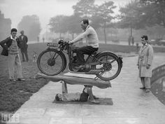 A 14-year-old boy supports a 200-lb-motorcycle and  its rider, circa 1932.
