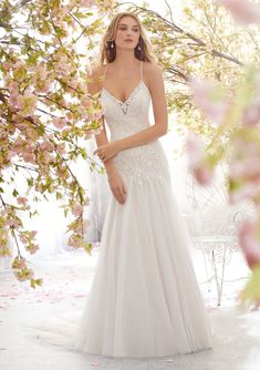 Shop Morilee's Lara Wedding Dress. This beautiful spaghetti strap Lara wedding dress features extraordinary beading and embroidery on an intricately designed net gown. Available in white, ivory, and ivory/nude, this v-neck neckline completes this fit and flare silhouette.