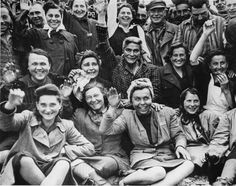 Liberated female prisoners at Dachau wave to their liberators. Date: Sunday, April 29, 1945.